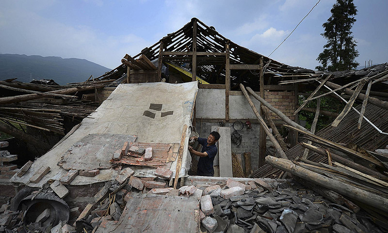 A man repairs a makeshift tent in front of a damaged house after last Saturday's earthquake in Longmen township of Lushan county, Sichuan province.—Photo by Reuters