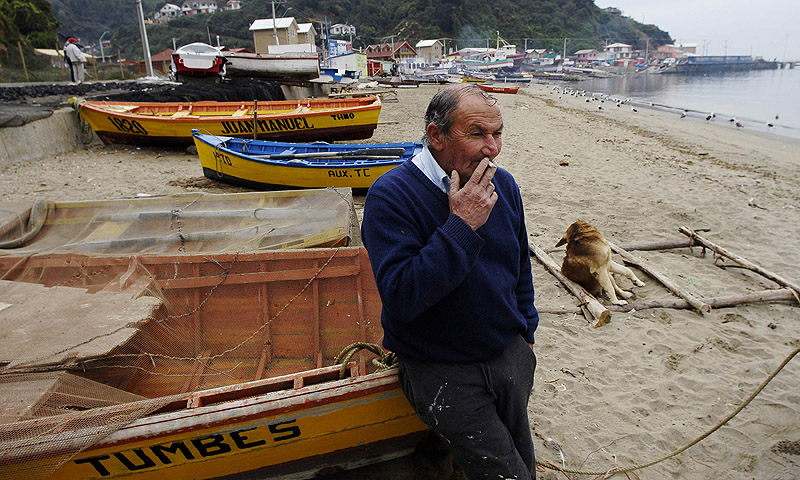 "An unemployed fisherman smokes a cigarette on the shores of ""Caleta Infiernillo"", a small fishing bay near Concepcion city, some 500 km south of Santiago. A rapidly declining stock of sardines and anchovies for the first time in 30 years due to overfishing and climate change has threatened livelihoods in the local artisanal fishing industry, affecting more than 6,000 people. Authorities are seeking ways to help fishing unions in the Bio Bio region tide over their losses this year, which have amounted to about $12 b"