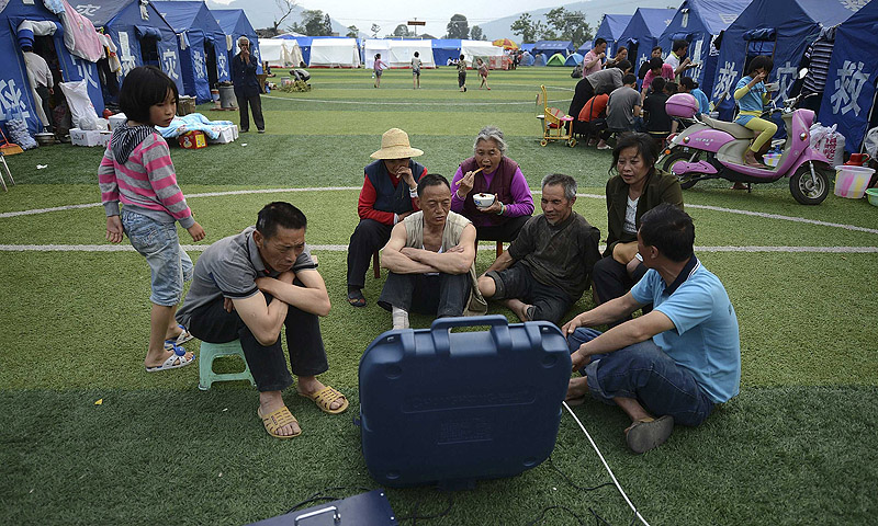 People watch television near their tents after last Saturday's earthquake in Longmen township of Lushan county, Sichuan province.—Photo by Reuters