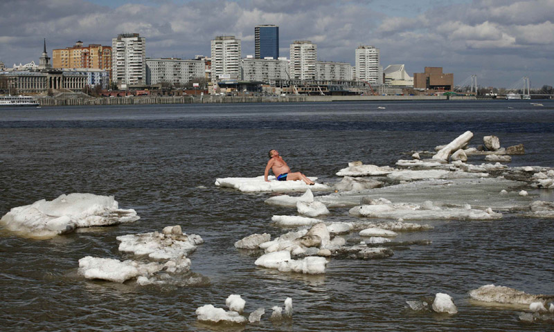 Vladimir Samsonov, 59, a resident from the Siberian town of Zheleznogorsk and a member of the Cryophil winter swimmers club, sunbathes as he sits on an ice floe on the Yenisei River in Krasnoyarsk.—Photo by Reuters