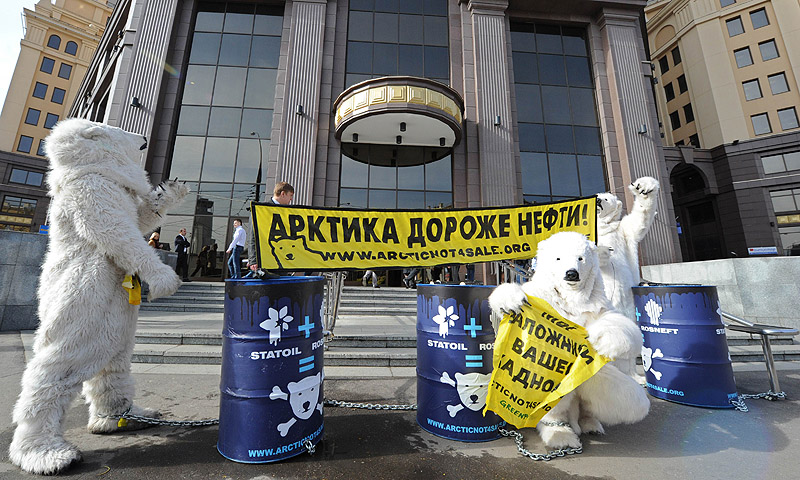 "Wearing polar bear costumes Greenpeace activist take part in a staged show against Norwegian oil and gas group Statoil's planned drilling in the Arctic, outside Statoil's office in Moscow. The yellow banner  (top) reads: ""Arctic is more valuable than oil!""  According to Greenpeace the staged show was aimed to draw attention to the threats of the catastrophic climate and  environment consequences of Arctic oil drilling.—Photo by AFP"
