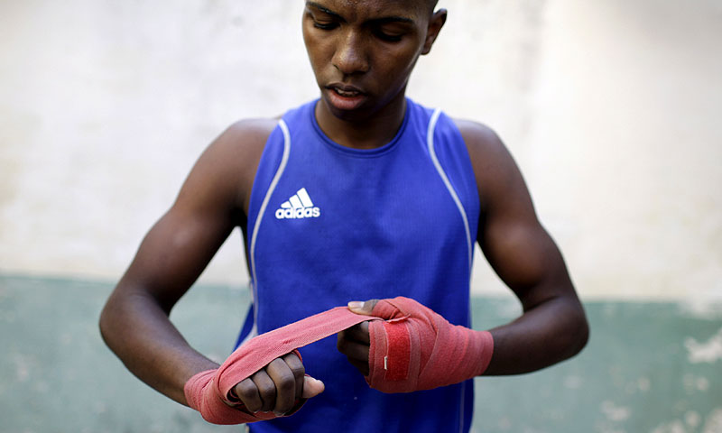In this March 16, 2013 file photo, boxer Osain Gonzalez prepares to compete in a local boxing tournament at the Rafael Trejos boxing gym in Old Havana, Cuba. -Photo by AP