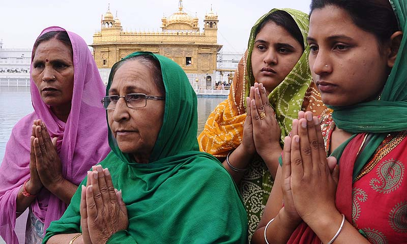 Members of Sarabjit Singh;s family pray for his well-being before their departure to Pakistan. — Photo by AFP