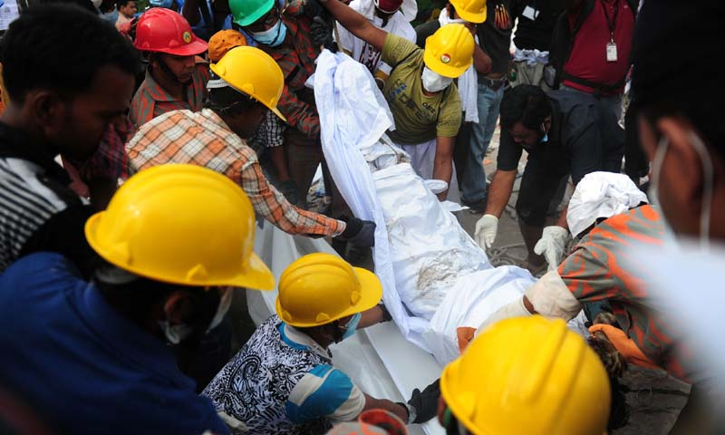 Bangladeshi volunteers and rescue workers recover a dead body from an eight-storey building that collapsed in Savar, on the outskirts of Dhaka on April 28, 2013. — AFP Photo