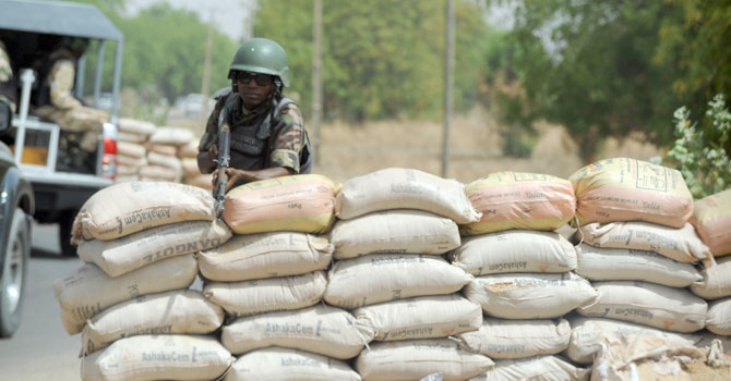 A Joint Military Task Force (JTF) soldier positions his rifle on sand bags on the road in northeastern Nigerian town of Maiduguri, Borno State, April 30, 2013. — Photo by AFP