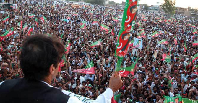 PTI chief Imran Khan holds his party's election symbol (bat) while addressing a public meeting. – Photo by INP