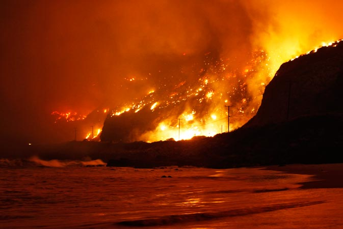 The Springs Fire rages along the Pacific Ocean north of the Ventura County Line. A wind-driven wildfire raging along the California coast north of Los Angeles prompted the evacuation of hundreds of homes and a university campus on Thursday as flames engulfed several farm buildings and recreational vehicles near threatened neighborhoods. —Reuters Photo