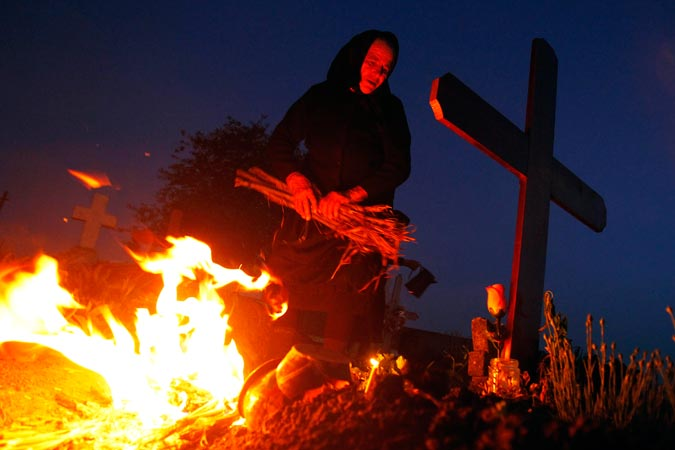 A woman lights a fire in front of the graves of her relatives at a cemetery in the village of Copaciu. Orthodox women went to church and cemeteries in the early morning on Maundy Thursday to light candles, burn incense and mourn their dead relatives as part of a southern Romania tradition. Maundy Thursday, or Holy Thursday, is the day Christians commemorate the Last Supper of Jesus Christ. Romania's Orthodox majority celebrates Easter on May 5. —Reuters Photo