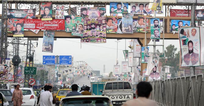 In this photograph taken on April 25, 2013, Pakistani commuters pass by electoral posters of candidates for the upcoming parliamentary elections displaying along a street in Rawalpindi. As Taliban bombs curtail campaign rallies, Pakistan's political parties are ploughing millions of dollars into TV and print advertising to sway voters ahead of next week's historic polls. - AFP Photo