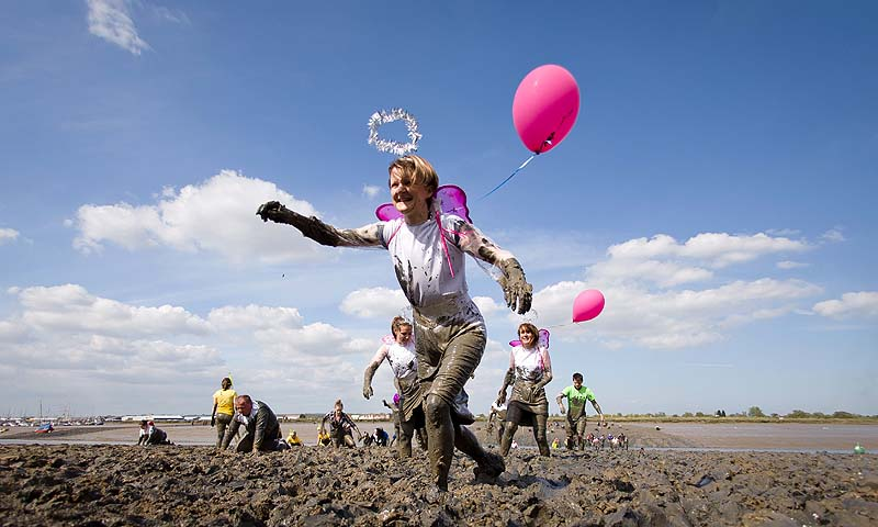 Participants reach the finish line of the annual Maldon Mud Race in Maldon, Essex, that sees people running on a short course across a muddy estuary in fancy dress to raise money for charities.—Photo by AFP