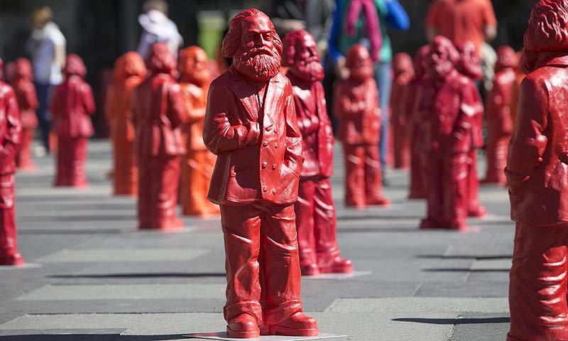 "Sculptures of the installation ""Karl Marx"" made of 500 figures featuring the communist icon stand in front of the landmark Porta Nigra in Marx' native town Trier,southwestern Germany. The installation by German artist Ottmar Hoerl is on display from May 5 to May 26, 2013 as part of the exhibition ""Icon Karl Marx"" hosted at the City museum Simeonsstift on the occasion of the 130th anniversary of the death of Karl Marx.—Photo by AFP"