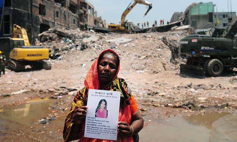 A Bangladeshi family member poses as she holds up the portrait of her missing relative, believed to be trapped in the rubble of an eight-storey building collapse in Savar, on the outskirts of Dhaka. The death toll from last week's collapse of a garment factory complex in Bangladesh has passed 500 as the country's prime minister said Western retailers had to share some of the blame for the tragedy. With bulldozers now clawing away at the mountain of rubble at the site of last Wednesday's disaster, the number of bodi