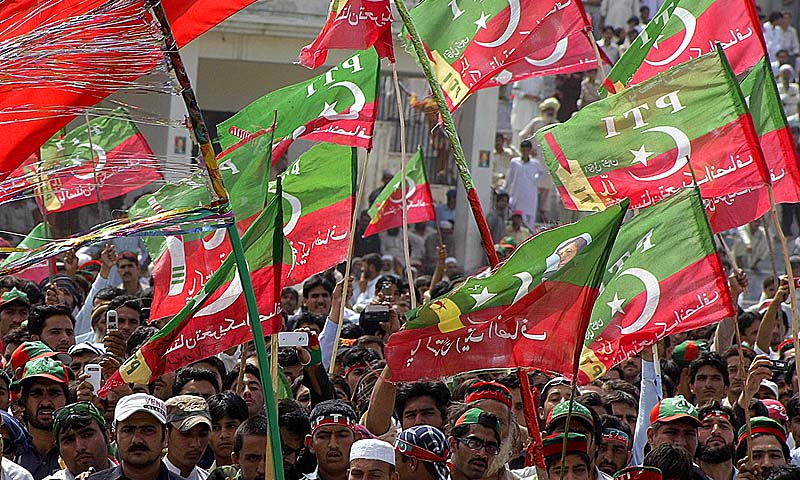 Supporters of Imran Khan, a Pakistani cricket legend and chairman of Pakistan Tehreek-e-Insaaf (PTI) or Movement for Justice party, wave party flags during a election campaign rally in Charsadda. A Pakistani candidate running for parliament in next week's historic election was injured on Saturday as his vehicle hit a roadside bomb in the troubled northwest, officials said.—Photo by AFP