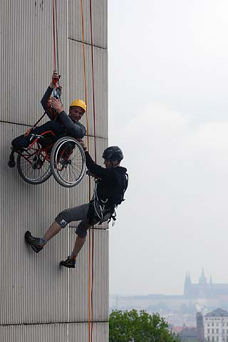 A handicapped young man from Jedlicka Institute, is helped by a climber during the first ever attempt to rappel from Prague's Congress Center in a wheelchair at an event to mark the institutes 100th founding anniversary in Prague. The Jedlicka Institute and Schools are a specialist educational establishment for children and young people primarily with a physical disability.—Photo by AFP