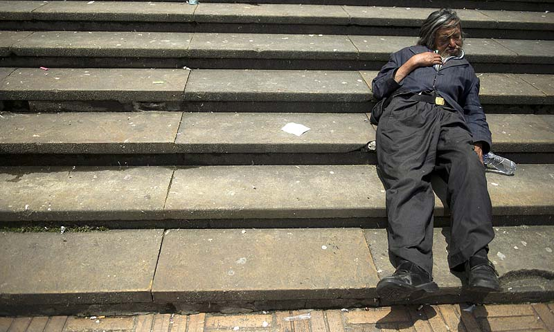 A beggar rests on the stairs of the Cathedral of Bogota at Bolivar Square in the Colombian capital as a group of activists demonstrate against abortion.—Photo by AFP
