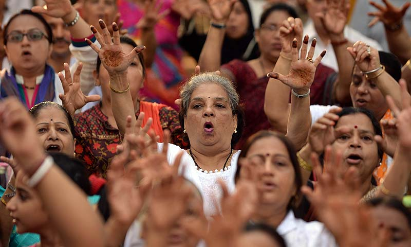 Indian women attend a laughter yoga session at a park during a World Laughter Day event in Mumbai. World Laughter Day which is celebrated on the first Sunday of May, was the brainchild and created in 1998 by Indian physician Dr. Madan Kataria, founder of the worldwide Laughter Yoga movement. The first World Laughter Day gathering took place in Mumbai, in 1998 with close to 10,000 people coming together in a mega laughter session.—Photo by AFP
