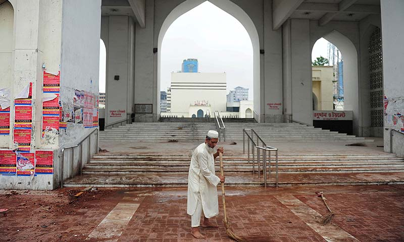 A Bangladeshi man cleans the premises of the national mosque Baitul Mukarram following a clash between police and Islamists, in Dhaka. At least 22 people were killed as Bangladeshi police fought pitched battles with tens of thousands of hardline Islamists in the capital Dhaka, police and medical officials said Monday.—Photo by AFP