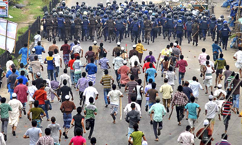 Protesters chase police during a protest, in Dhaka, Bangladesh. The Islamic activists have been holding protests to demand that the government implement an anti-blasphemy law.—Photo by AP
