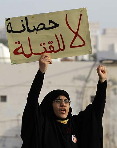 "A Bahraini anti-government protester holds a sign in Arabic that reads, ""no immunity for killers,"" during clashes in Diraz, Bahrain. Large numbers of riot police stormed the area just ahead of a planned demonstration in support of jailed activists, chasing away demonstrators as they arrived for the march.—Photo by AP"