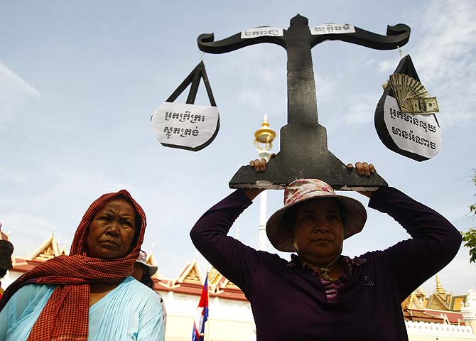 A protester from Boeung Kak lake holds a cutout of a scale symbolizing justice as she joins other villagers, who were allegedly evicted from their homes without adequate compensation, during a rally in front of the Justice Ministry in Phnom Penh, Cambodia. Phnom Penh's Boueng Kak is a lake area the government awarded to a Chinese company for commercial development including a hotel, office buildings and luxury housing. The letters on the sign read, clockwise from left: Poor villagers are gentle, Independence, Justi