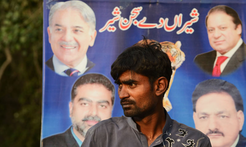 A man stands in front of an election poster during a political rally in Lahore on the last day of election campaigns. -AFP Photo