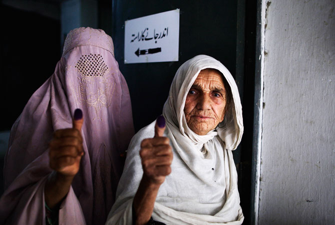 Pakistani women show their election ink-stained thumbs after casting their ballots at a polling station on the outskirts of Islamabad, Pakistan. —AP Photo