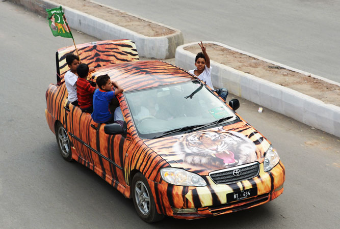 Supporters of PML-N drive through the streets during the general election in Rawalpindi. —AFP Photo
