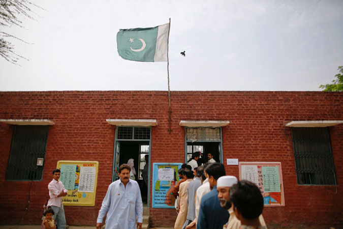 A flag and a bird fly over a polling station as people wait to cast their votes in a village near Lahore. —Reuters Photo