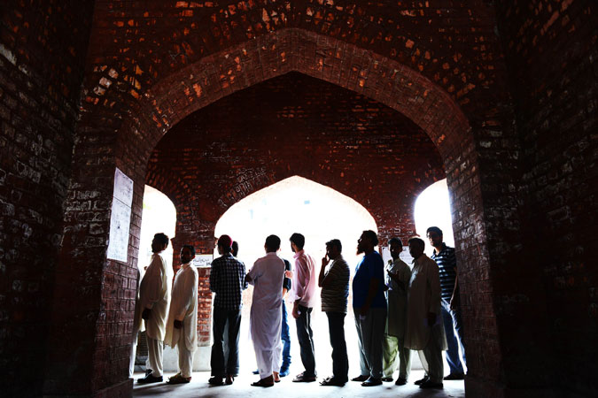 Voters wait in line under arches at a polling station in Lahore during the general elections in Pakistan. —AFP Photo
