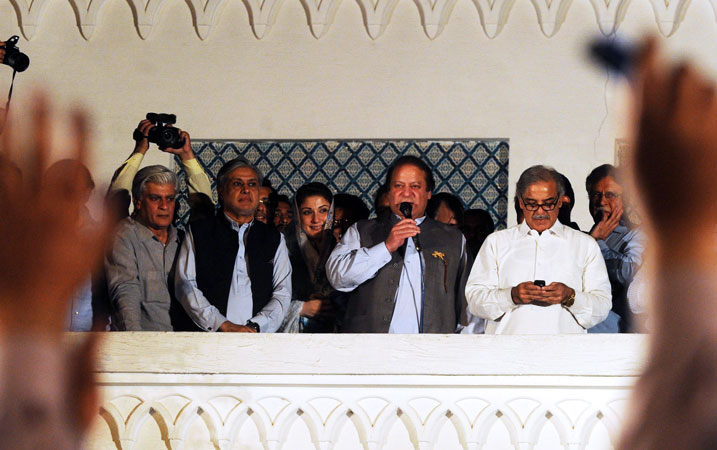 Former Pakistani Prime Minister and head of the PML-N, Nawaz Sharif (C) is flanked by his brother Shahbaz Sharif (R) as he addresses the supporters after his party's victory in general election in Lahore. Sharif declared victory for his centre-right party in Pakistan's landmark elections on May 11, as unofficial partial results put him on course to win a historic third term as premier. The result represented a remarkable comeback for a man who was deposed as premier in a 1999 military coup. —AFP Photo