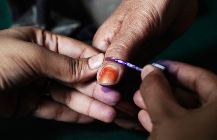 An election official marks a voter's thumb with ink for identification as she gets a ballot paper before casting her vote at a polling station in Peshawar. —Reuters Photo
