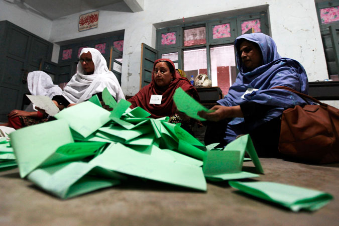 Election workers count ballots after polls closed for Pakistan's general elections in Peshawar. —Reuters Photo