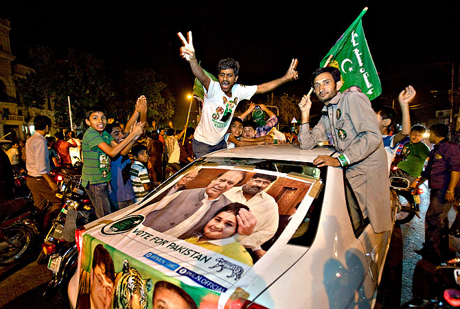 Supporters of Pakistan Muslim League-N party celebrate the primary unofficial results of their country's parliamentary elections in Lahore, Pakistan Saturday, May 11, 2013. — AP Photo
