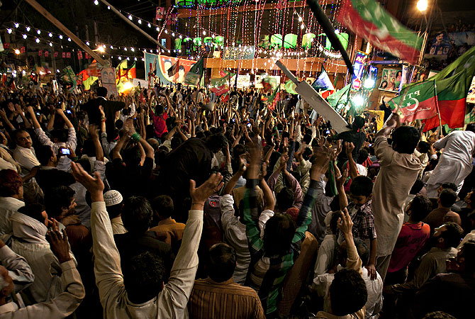 Supporters of Tehreek-e-Pakistan, headed by Pakistan's cricketer-turned-politician Imran Khan, celebrate the victory of their supported candidate in Rawalpindi, Pakistan on Saturday, May 11, 2013.— AP Photo