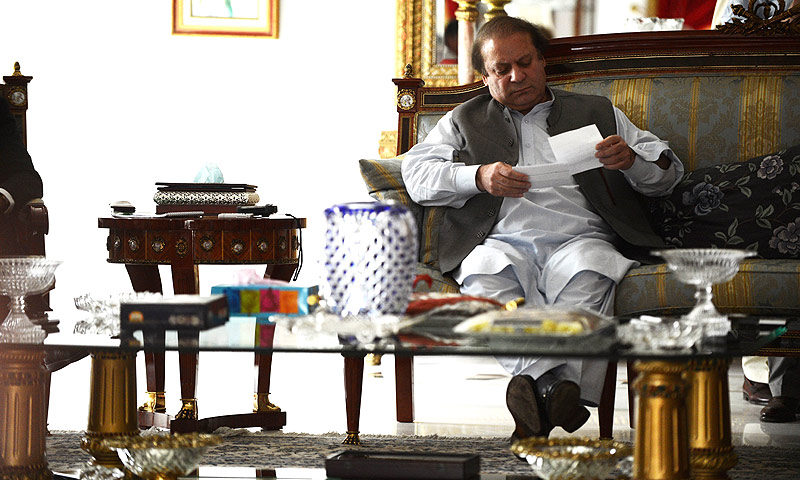 Nawaz Sharif reads notes handed to him at his farm house in Raiwind on the outskirts of Lahore on May 13, 2013. -Photo by AFP
