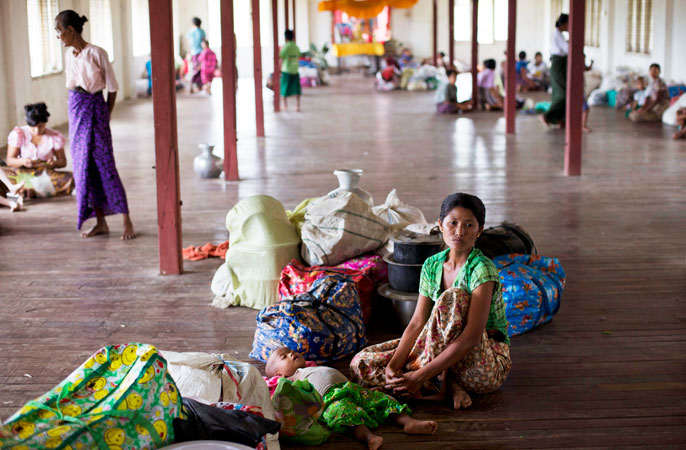 A Rakhine Buddhist woman and her child, whose family took temporarily shelter in a monastery because of the arrival of the Cyclone Mahasen, sits on the floor with their belongings at a Buddhist monastery in Sittwe, northwestern Rakhine State, Myanmar. —AP Photo