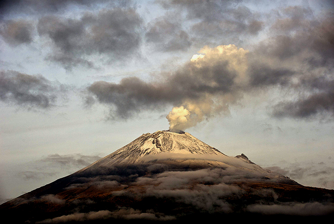 "The Popocatepetl Volcano, Mexico's second highest peak just 55 km southeast of Mexico City, is seen from Santiago Xalitxintla, in Puebla, on May 14, 2013 spewing a cloud of ash and smoke. The National Disaster Prevention Centre (CENAPRED) raised the alert level on Sunday to ""yellow phase three"". — AFP Photo"