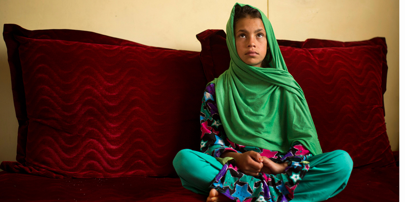 """Zardana, 11, sits as she talks in Kandahar, Afghanistan on Monday, April 22, 2013 about a pre-dawn last year when a U.S. soldier burst into her family's home. Zardana said her visiting cousin saw the soldier chasing them and ran to help, but he was shot and killed. """"We couldn't stop. We just wanted somewhere to hide. I was holding on to my grandmother and we ran to our neighbors.""""  — AP Photo."""
