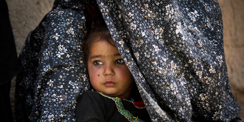 Shahara, now 3, sits tucked inside the shawl of her mother, Masooma, in Kandahar, Afghanistan, on Saturday, April 20, 2013 as Masooma recalls the night she says a U.S. soldier killed her husband and attacked her children in a southern Afghanistan village. Masooma says the soldier grabbed Shahara's pony tails and shook her head violently after killing her father.  — AP Photo.