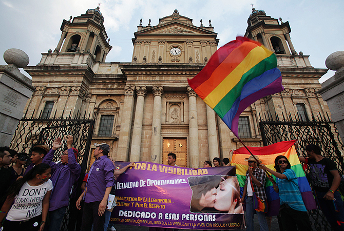 Activists hold rainbow flags and a banner as they gather in front of the city cathedral demanding the recognition of gay rights and the legalization of gay marriages, to mark International Day Against Homophobia and Transphobia in Guatemala City May 17, 2013. — Reuters Photo