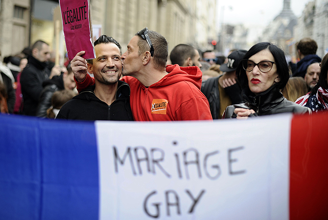 A picture taken on December 16, 2012 in Paris shows a man kissing his companion during a demonstration for the legalisation of gay marriage and LGBT (lesbian, gay, bisexual, and transgender) parenting. France became the 14th country to legalise same-sex marriage on May 18, 2013 after President Francois Hollande signed the measure into law following months of bitter political debate.  Hollande acted a day after the Constitutional Council threw out a legal challenge by the right-wing opposition, which had been the la