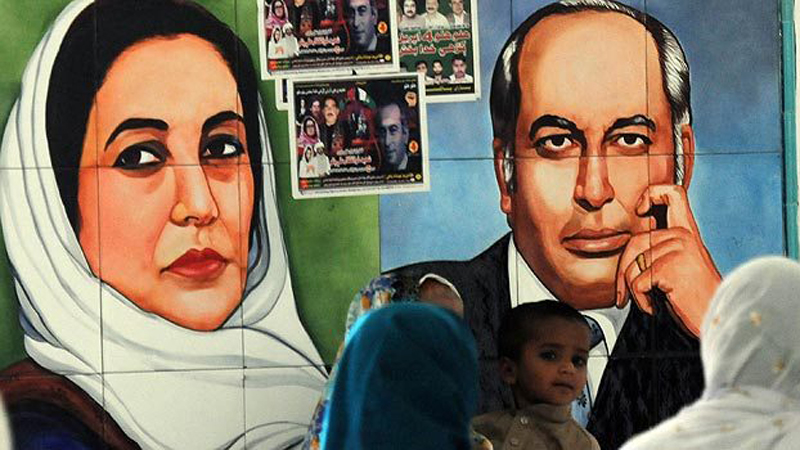 Supporters of Pakistan People's Party (PPP) walking past the portraits of former premier Zulfiqar Ali Bhutto (R), father of Pakistan's slain former premier Benazir Bhutto (L), at the Bhutto's mausoleum in Garhi Khuda Bakhsh. -Photo by AFP