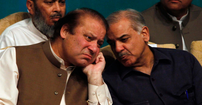 Nawaz Sharif talks with his brother Shahbaz Sharif before addressing the newly elected lawmakers belonging to PML-N, during a function in Lahore on May 20, 2013. – Reuters Photo