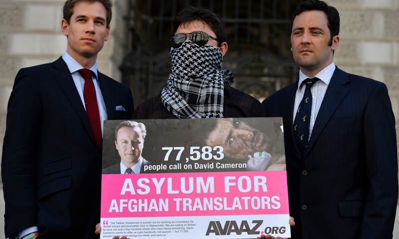 A picture dated May 3, 2013 shows former British servicemen Patrick Hemessey (L) and Jake Wood (R) posing with an interpreter named only as Mohammed (C) at the Foreign and Commonwealth Office in central London before delivering a petition signed by over 70,000 people calling for assylum for Aghan interpreters who served the British army.  AFP File Photo