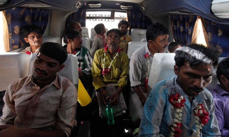 Fishermen from India wear garlands as they sit in a bus after their release from a prison in Karachi, May 24, 2013. — Photo by Reuters