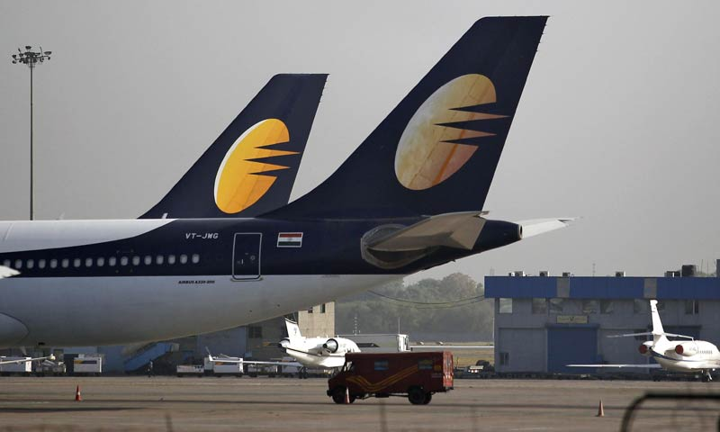 An India Post mail van moves past a parked Jet Airways passenger plane at the Indira Gandhi International Airport in New Delhi May 24, 2013. Shareholders in India's Jet Airways approved an agreed sale of a 24 percent stake in the airline to Abu Dhabi's Etihad Airways, a senior executive at the Indian carrier said on Friday. - Reuters