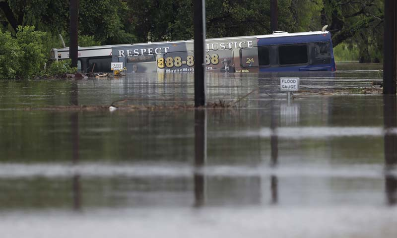 A San Antonio metro bus sits in floodwaters after it was swept off the road during heavy rains, Saturday, May 25, 2013, in San Antonio. — Photo by AP