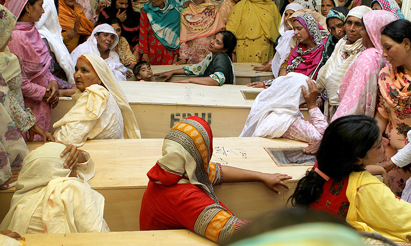 Pakistani women, mourn next to the bodies of friends and relatives. — AP Photo