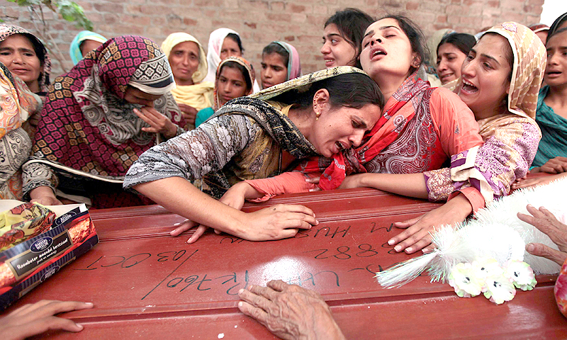 Relatives of one of 14 children, who died after a gas cylinder exploded on a school bus, mourn over his coffin, on the outskirts of Gujrat, 100 miles (170 km) southeast of Islamabad. — Reuters Photo