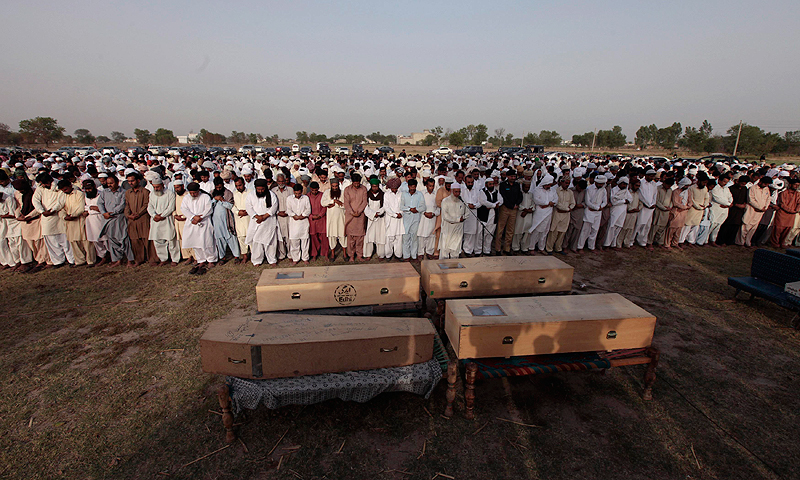 People pray over the coffins of children who died after a gas cylinder exploded on a school bus. — AP Photo